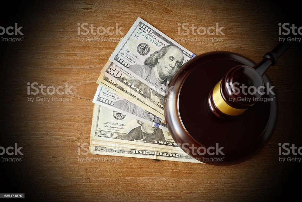 Hammers's judiciary with dollars on wooden background. stock photo