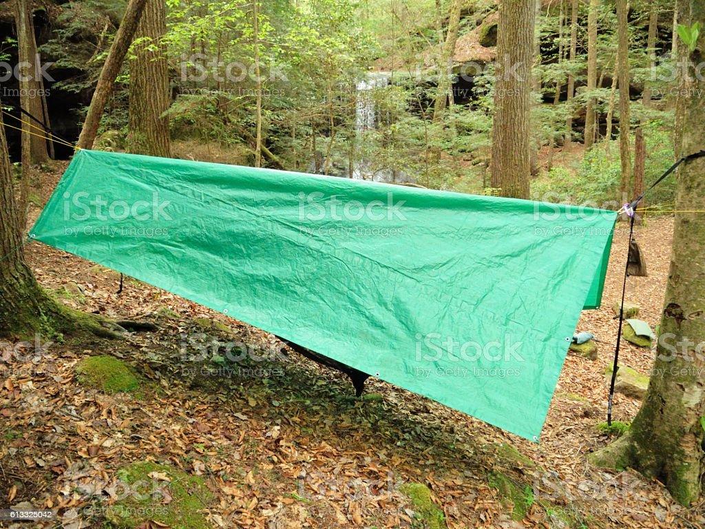 Hammock hanging under green tarp by watefall stock photo