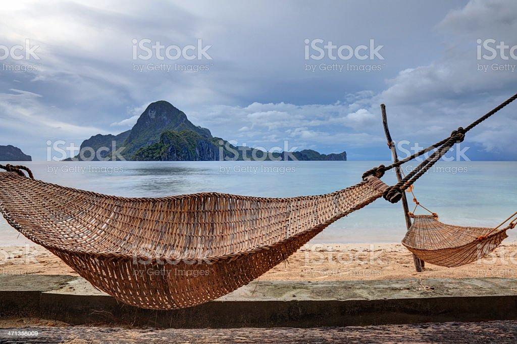 Hammocks anchored between palm trees on a sand beach stock photo