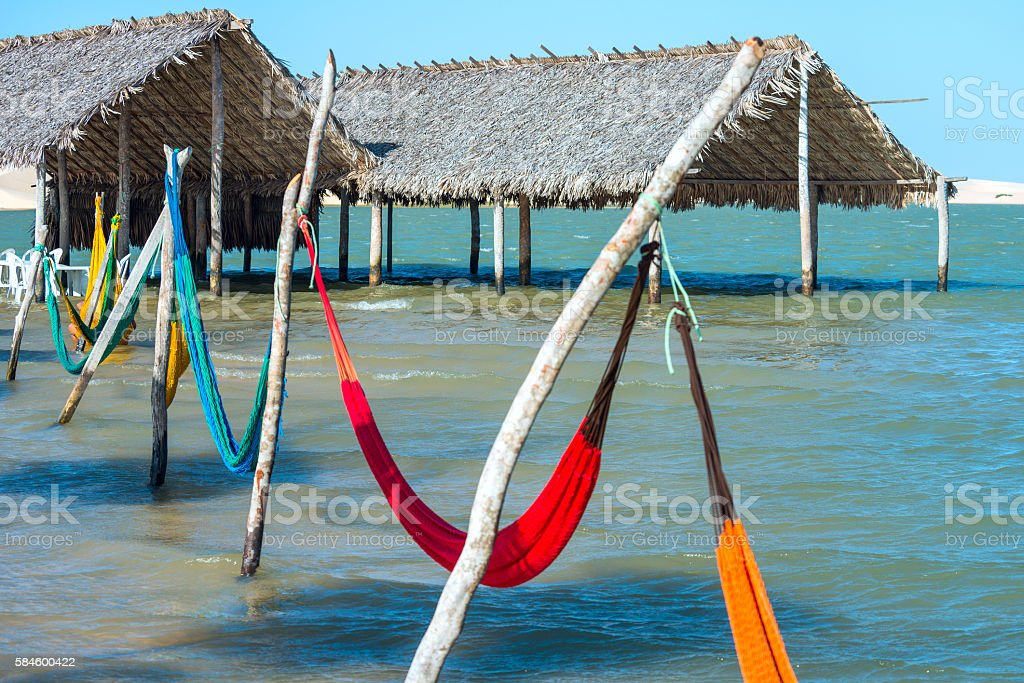 Hammocks under the shade of palapa sunroof in Jericoacoara, Brazil stock photo
