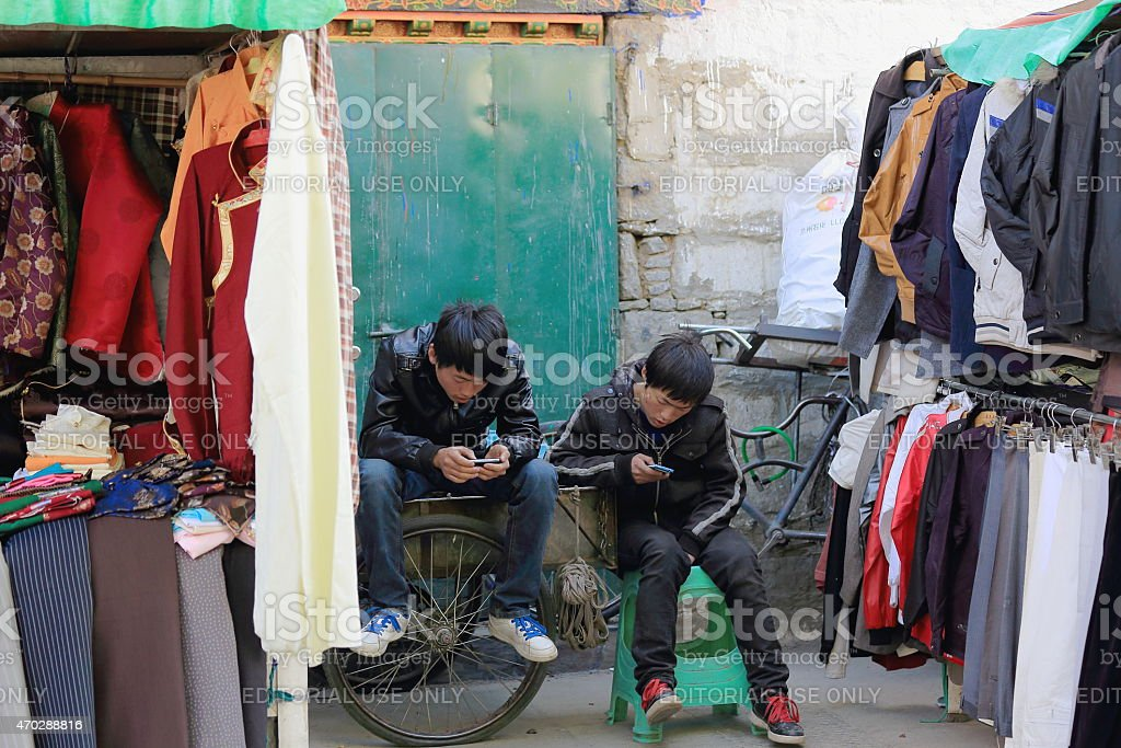 Han people youngsters with e-game devices. Lhasa-Tibet. 1333 stock photo