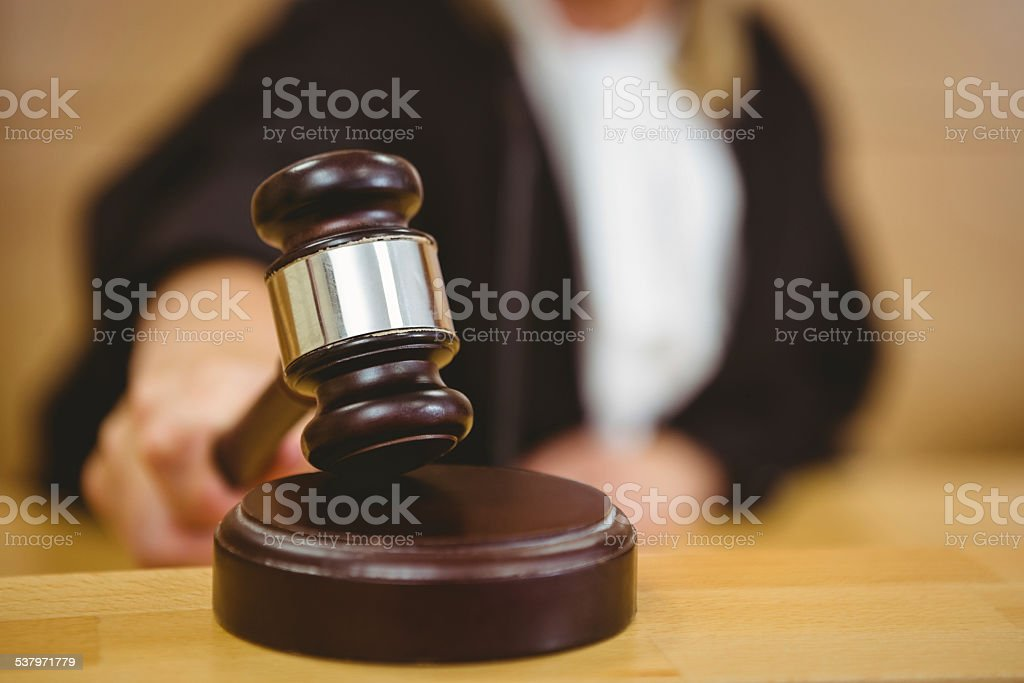 Hand about to bang gavel on sounding block stock photo