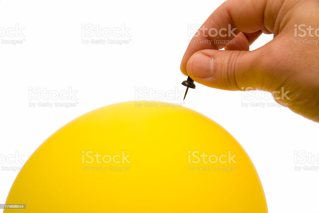 A hand about to prick a balloon with a pin to cause surprise stock photo