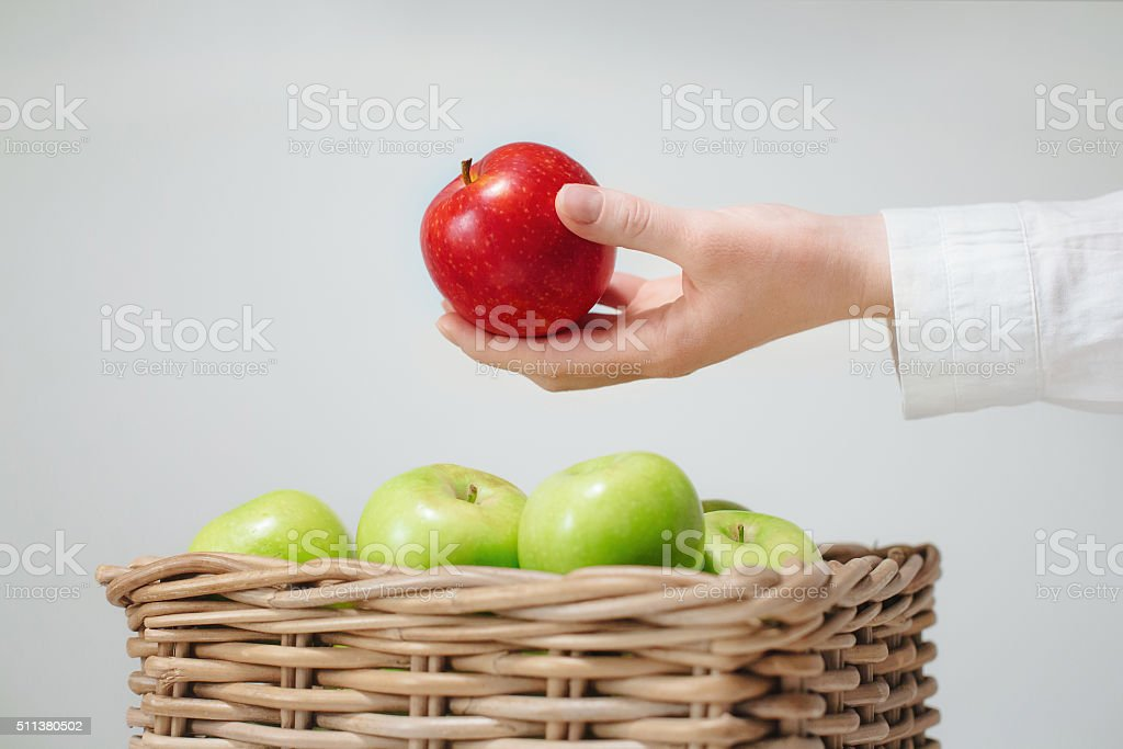hand above basket  with green apples and red stock photo