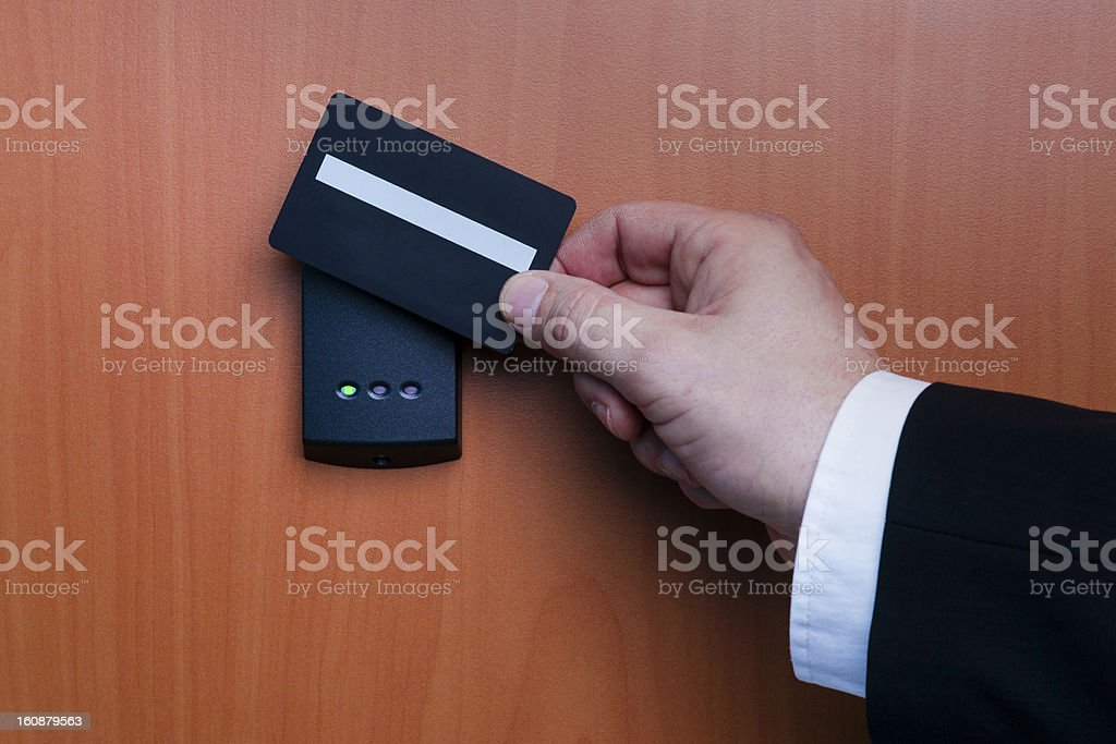 Hand activating an electronic security system with a card stock photo