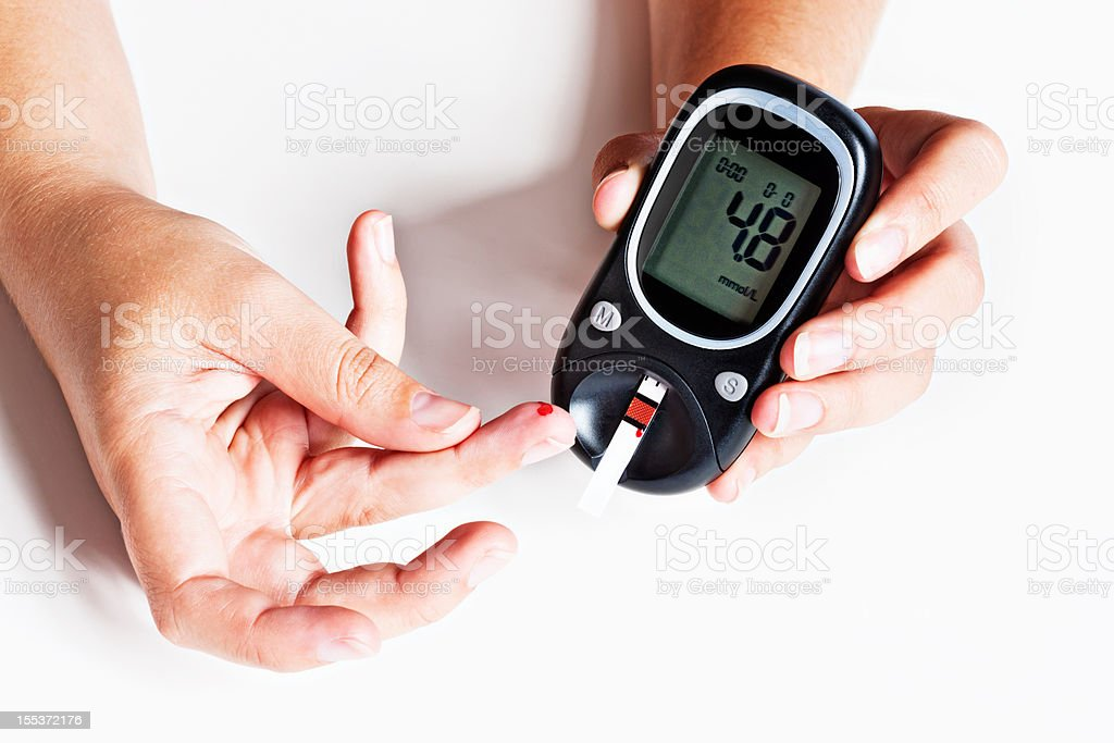 Hand adding drop of blood to diabetic glucometer royalty-free stock photo