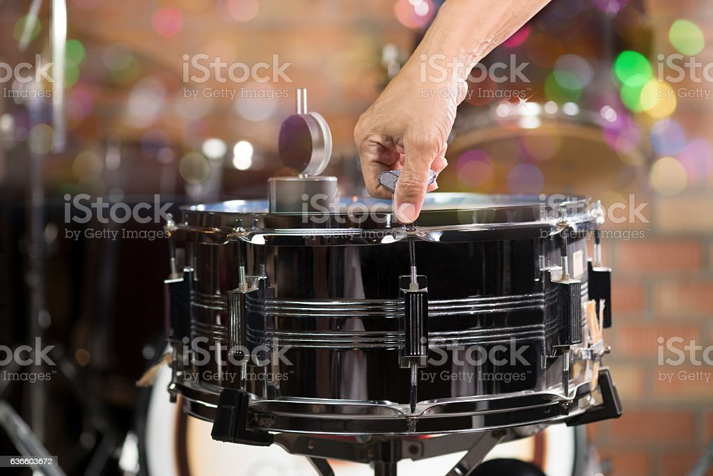 Hand adjusting tension rod of snare drum. stock photo