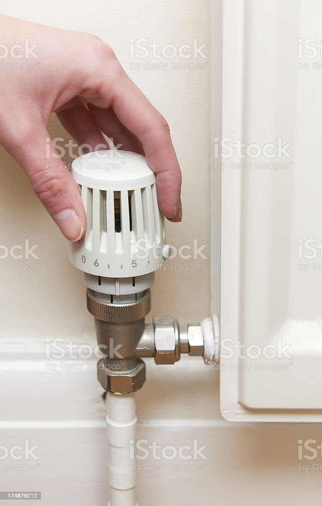 Hand Adjusting Thermostat On Radiator Valve royalty-free stock photo