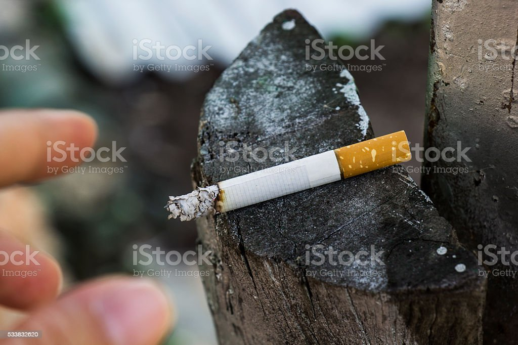 Hand and a cigarette on a wooden background. Addiction concept stock photo