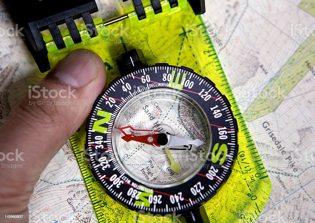 hand and compass on map stock photo