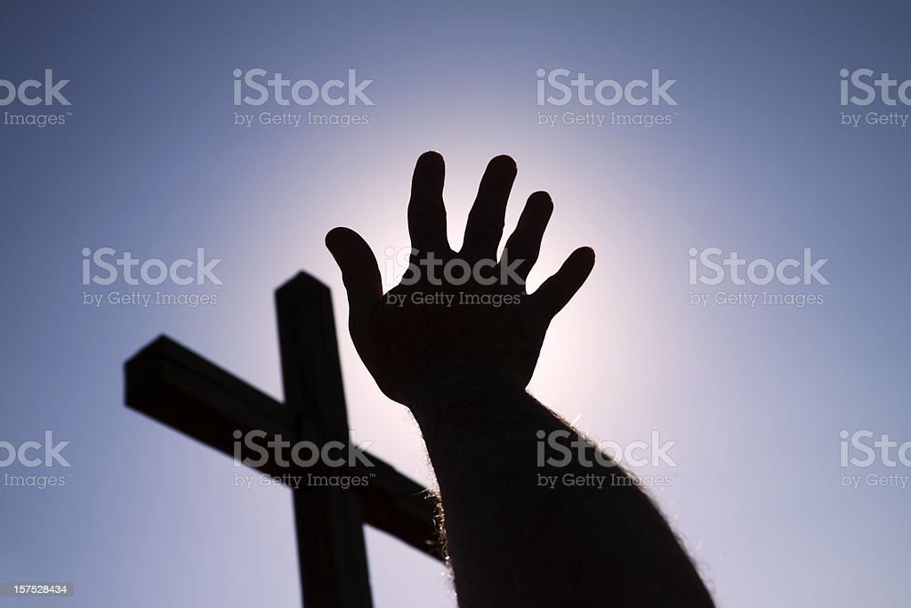 Hand and cross in silhouette royalty-free stock photo