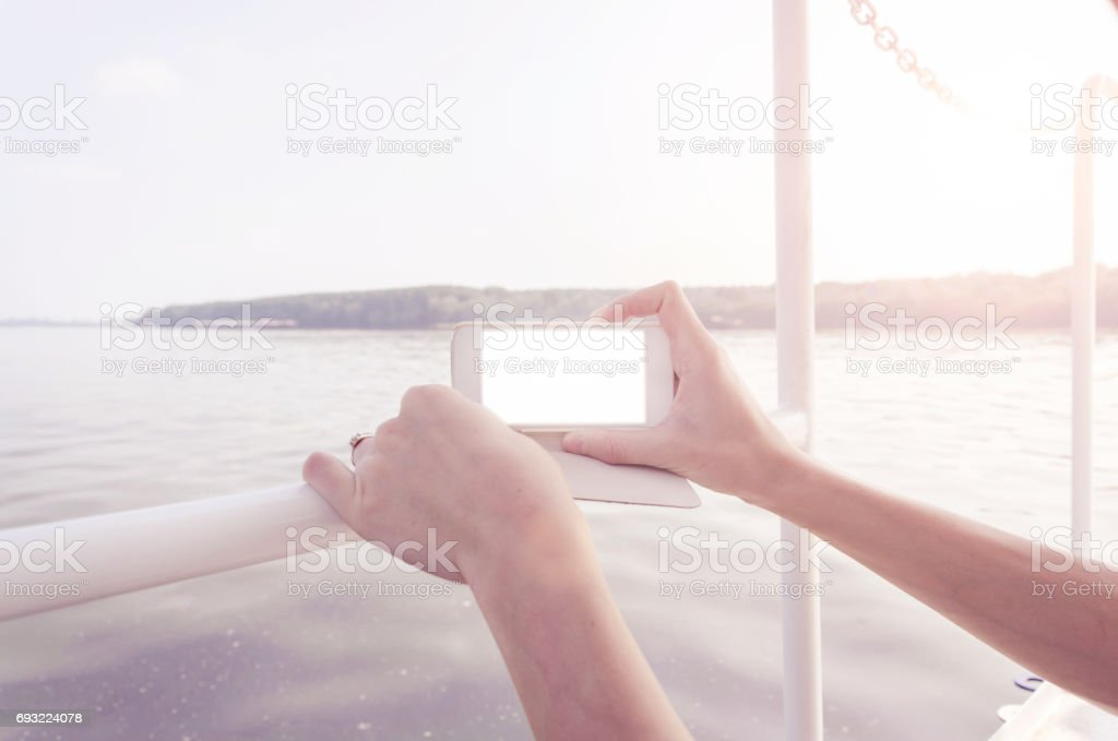 hand and mobile phone in your hand by the river stock photo
