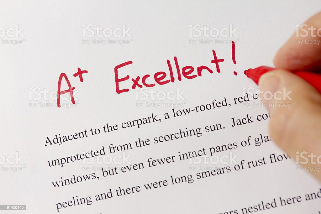 Hand and Red Pen Grading Successful Essay with Excellent stock photo