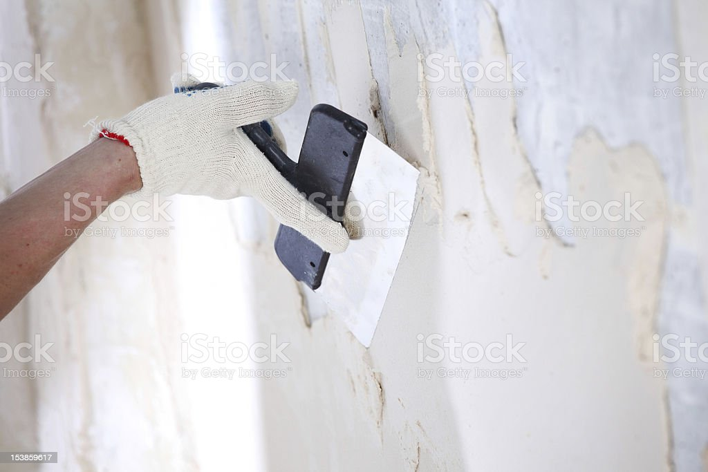 Hand applying render to a wall royalty-free stock photo