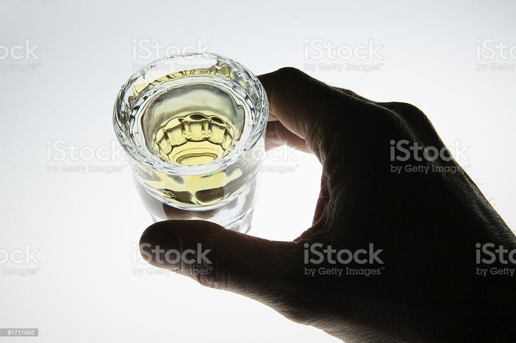 Hand around shot glass of liquor royalty-free stock photo