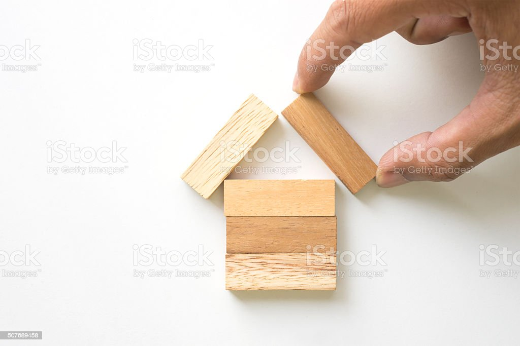 Hand arranging wood block as house. stock photo