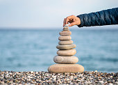 Hand balancing stack of stones on beach