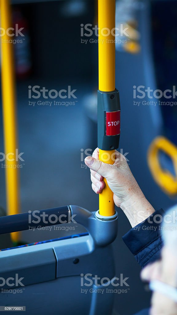 Hand below stop button in bus stock photo