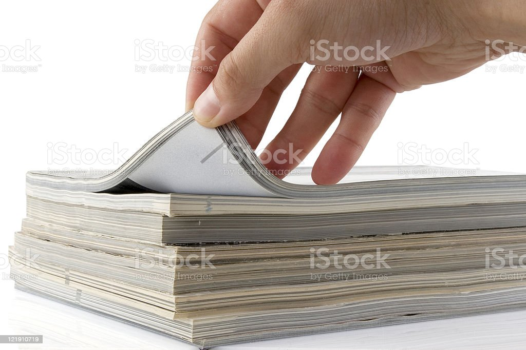 hand browsing through stack of magazines royalty-free stock photo
