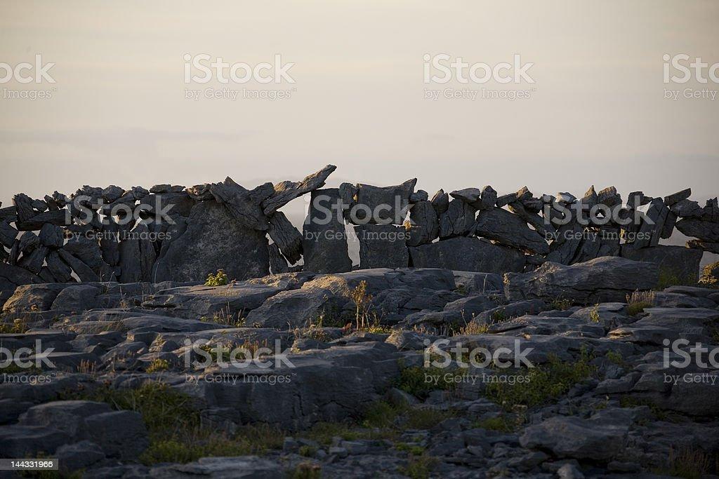 Construction de mur de pierres dans la main au coucher du soleil photo libre de droits