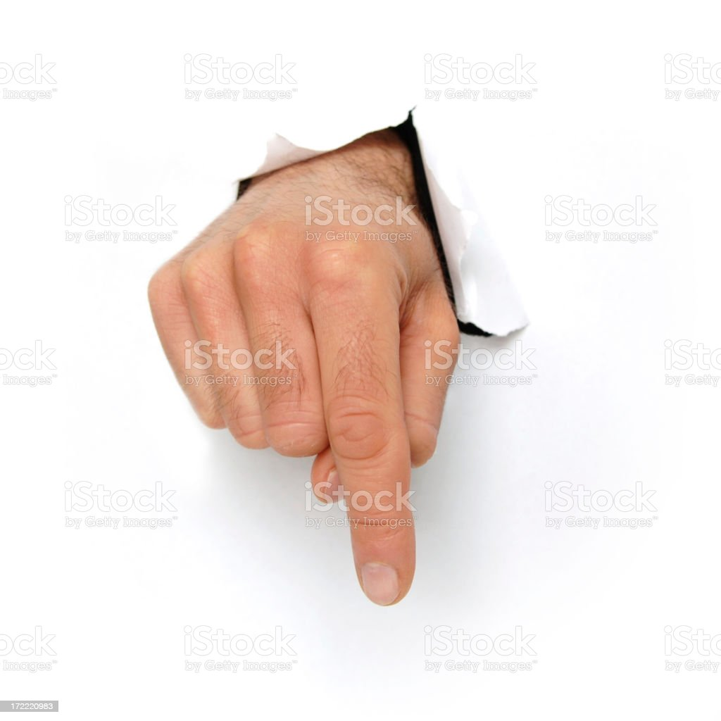 Hand bursting through white card pointing down stock photo