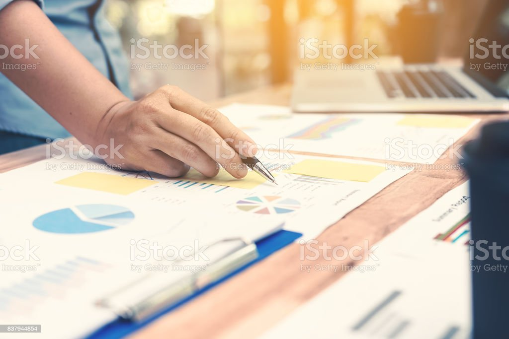 Hand business woman pointing paper data analyze chart on desk at office room. stock photo