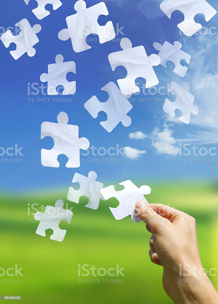 A hand catching a falling puzzle piece royalty-free stock photo