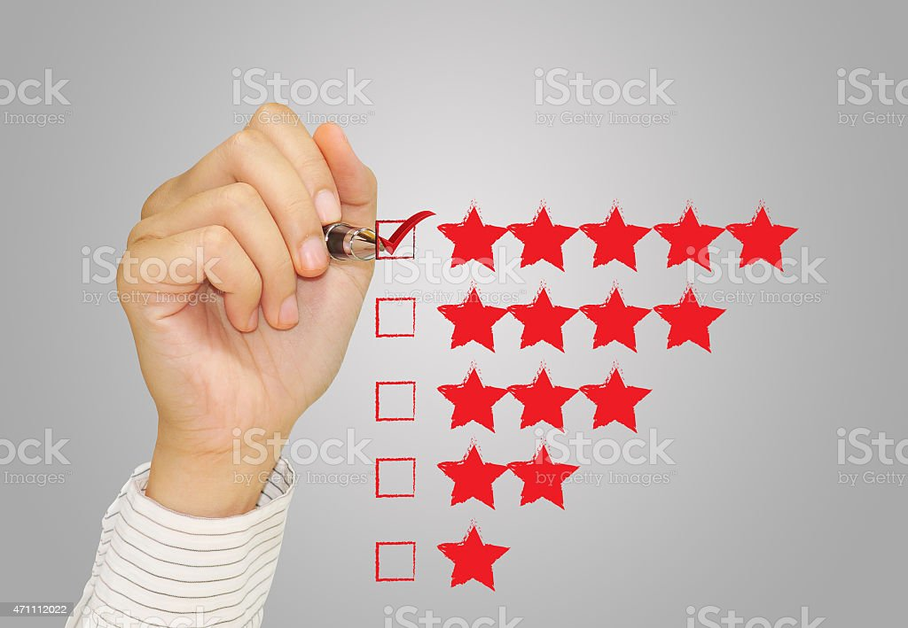 Hand check mark with red marker on five star rating. stock photo