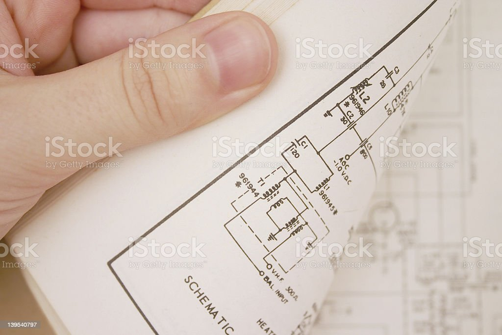 Hand checking electronics book stock photo