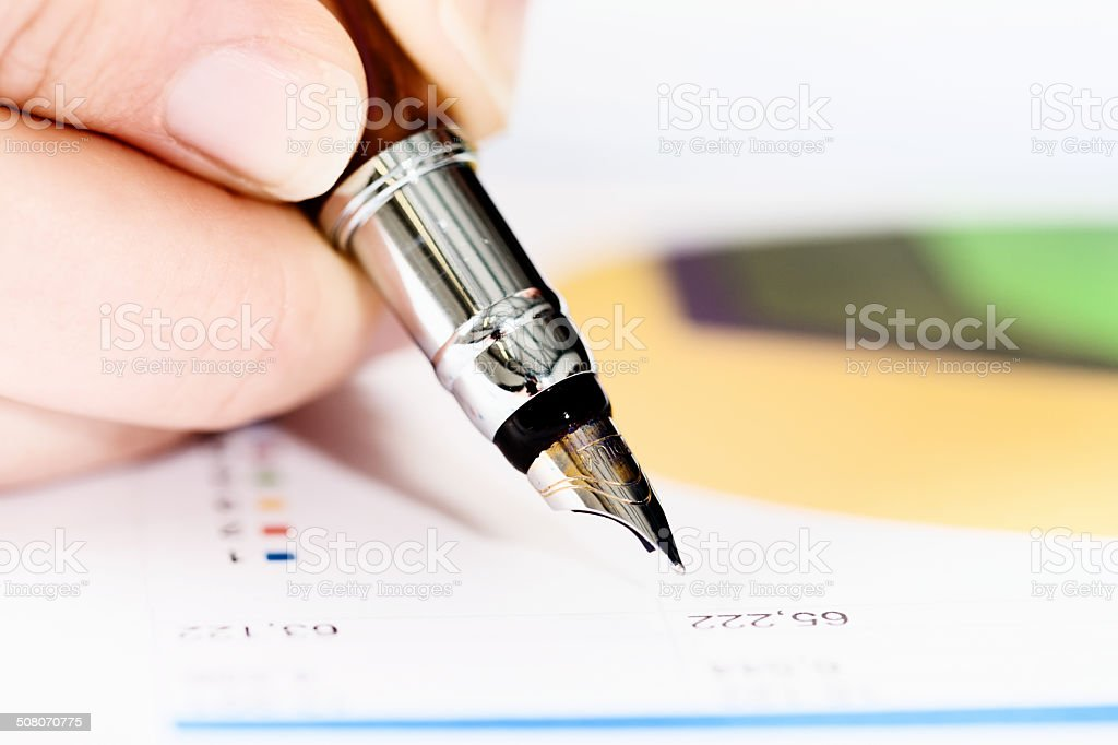 Hand checking spreadsheet with fountain pen, pie chart in background royalty-free stock photo