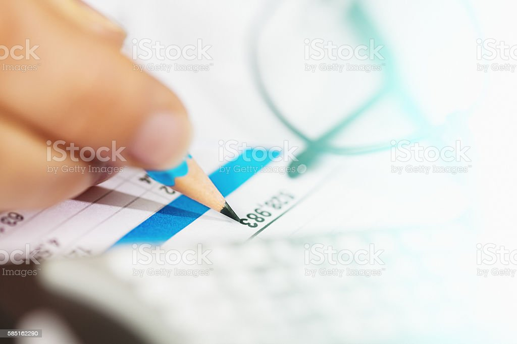 Hand checks figures on financial document with pencil stock photo