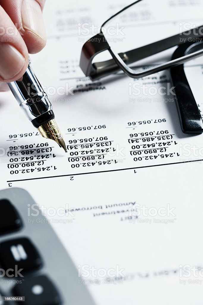 Hand checks items on financial document, spectacles and calculator nearby royalty-free stock photo