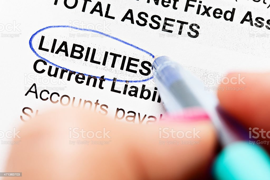 Hand circles word 'Liabilities' using ballpoint pen royalty-free stock photo
