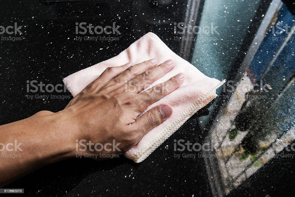 Hand cleaning black marble stone counter bar stock photo