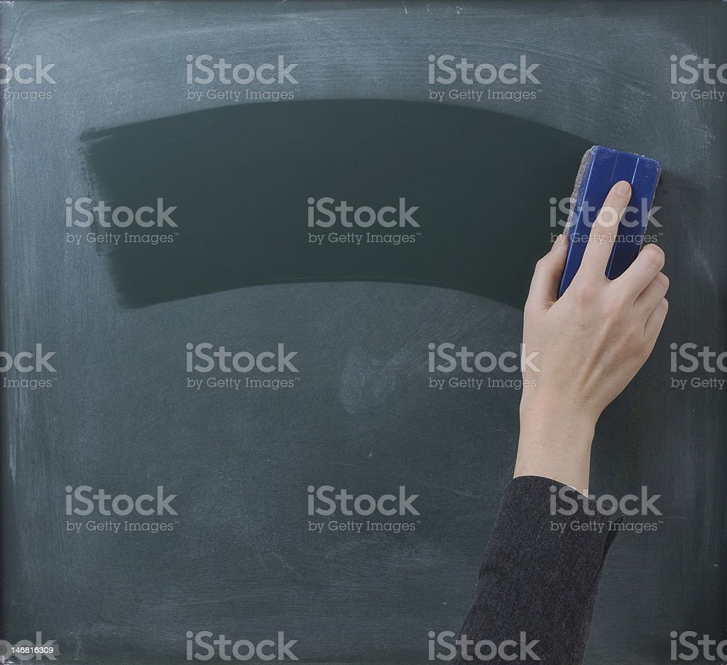 Hand cleaning blackboard with chalkboard rubber stock photo