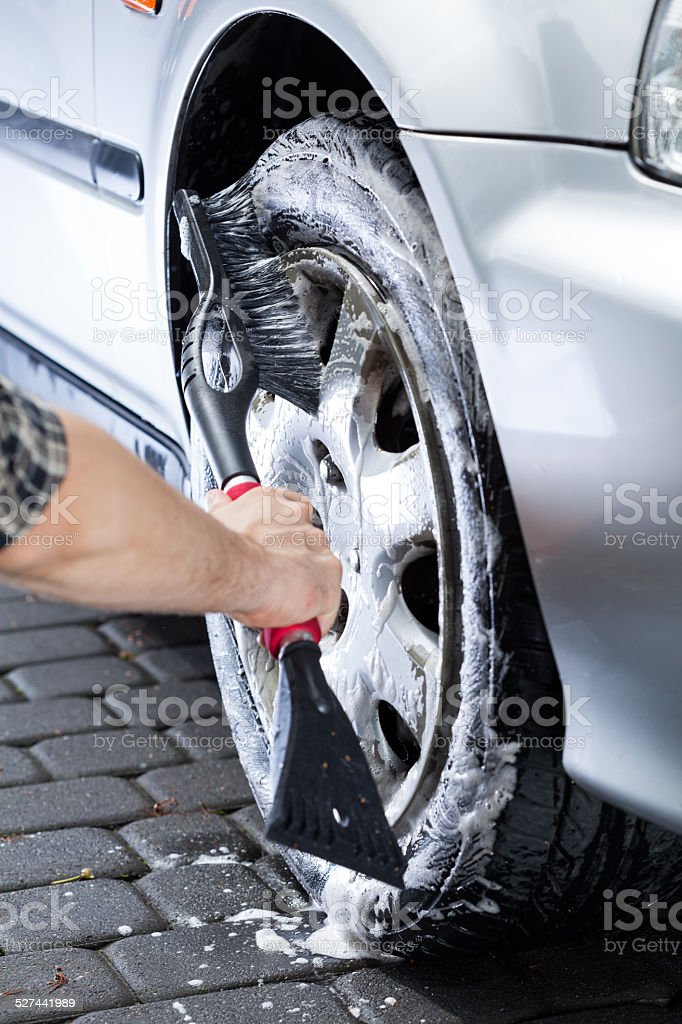 Hand cleaning car wheel stock photo