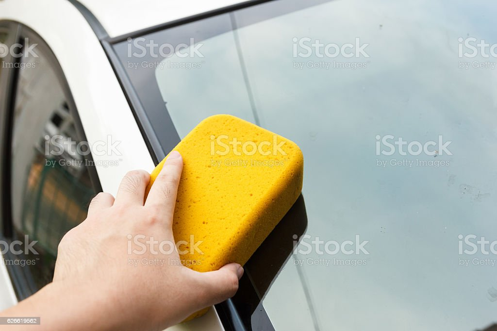 Hand cleaning car's dirt with sponge. stock photo