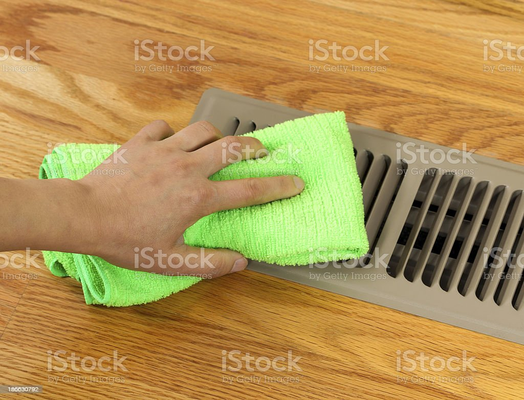 Hand Cleaning Grill Plate of Floor Heating Vent in Home stock photo
