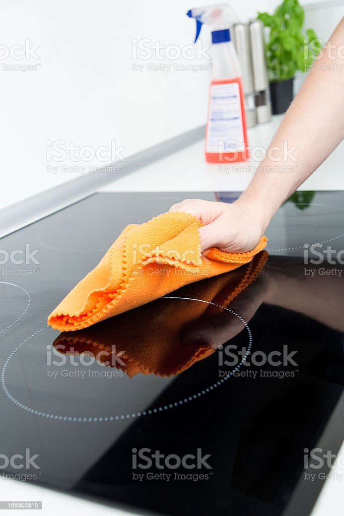 Hand cleaning induction stove royalty-free stock photo