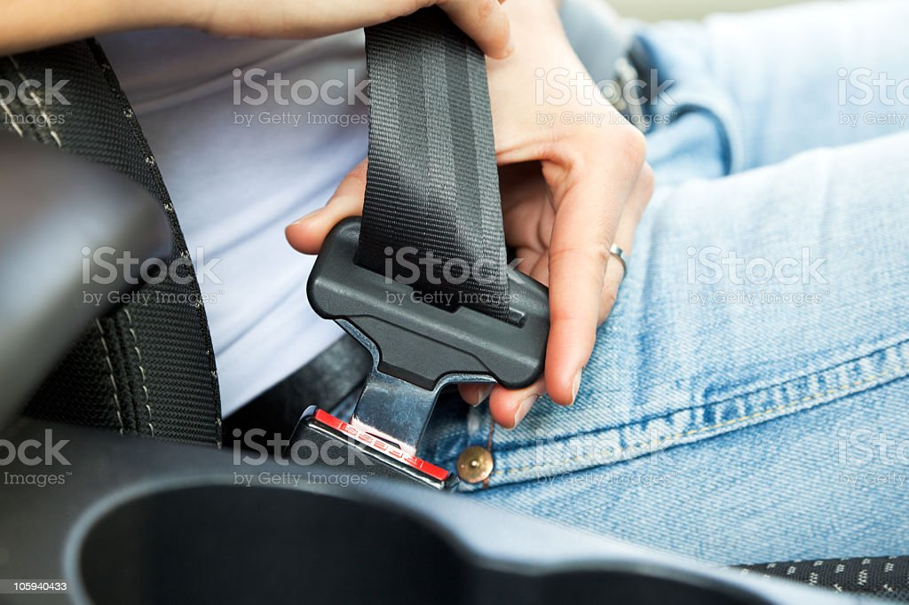 Hand clicking in a seatbelt in a car stock photo