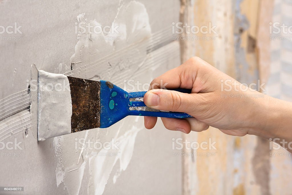 hand coating wall of plaster stock photo