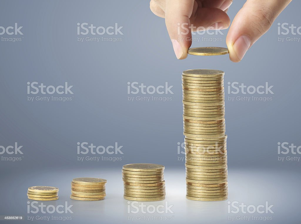 hand coins in finger and row stacks them royalty-free stock photo