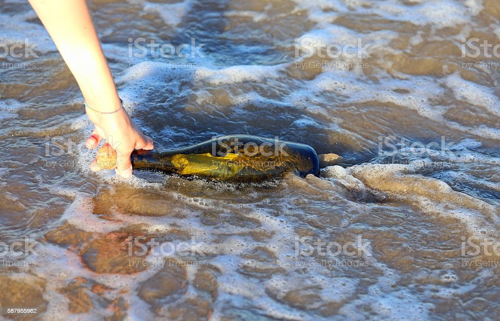 hand collecting bottle on the Beach stock photo