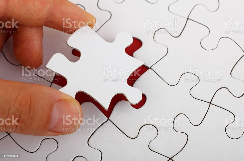 Hand completing a blank jigsaw puzzle stock photo