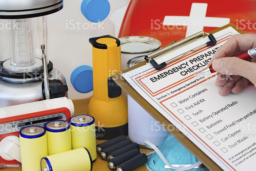 Hand completing Emergency Preparation List by Equipment royalty-free stock photo