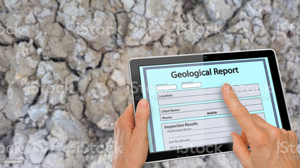 Hand completing online Geological Report on a computer tablet - infront of clay soil background stock photo