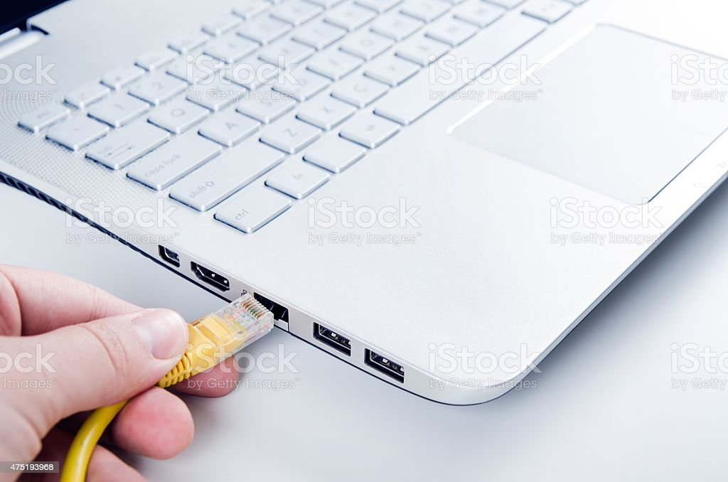 Hand connecting ethernet cable to lan port stock photo