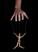 Hand controlling wooden puppet, low key images, on black background