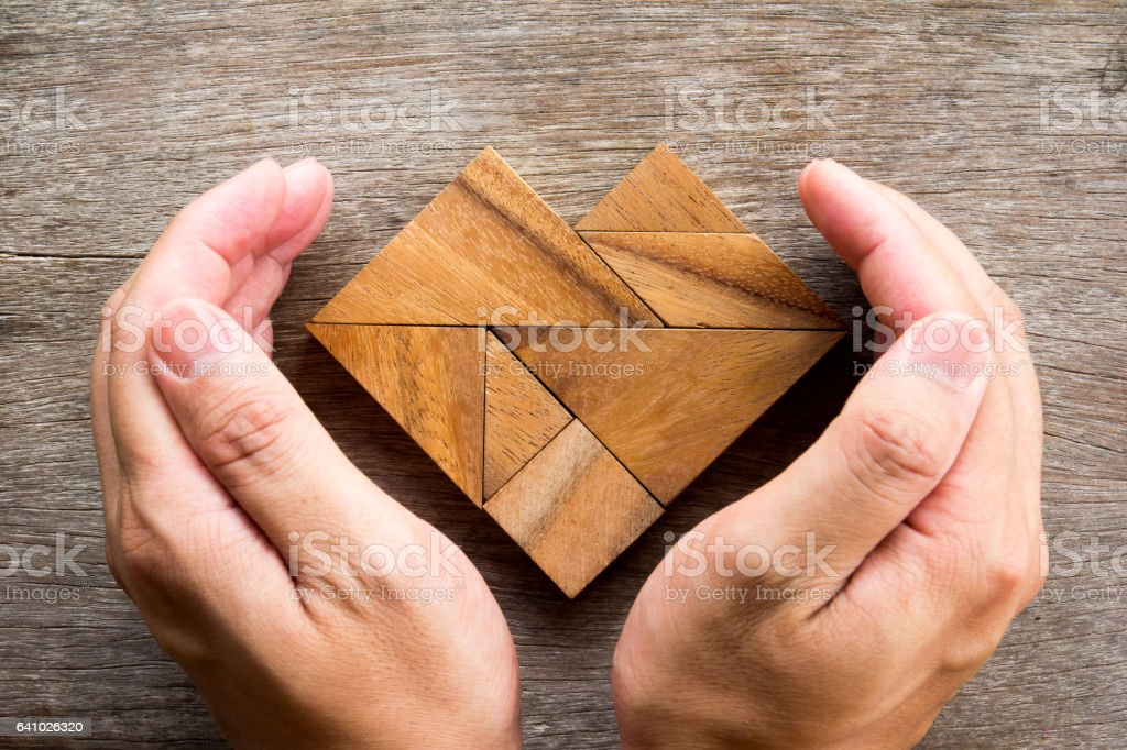 Hand cover tangram puzzle in heart shape on wooden background stock photo