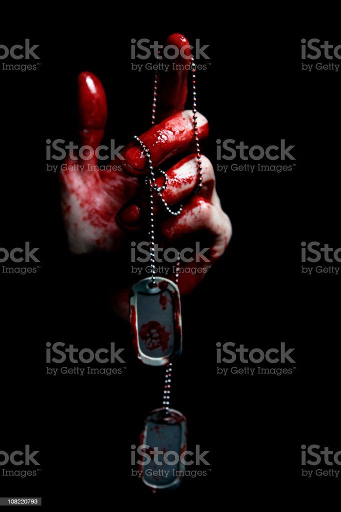 Hand Covered in Blood Holding Dog Tags royalty-free stock photo